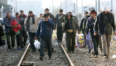 ASYLUM SEEKERS WALKING ALONG A RAILWAY LINE IN CALAIS. The mayor of Calais has admitted that another asylum centre is to be built.